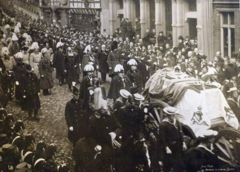 Photograph of the funeral of Queen Victoria with the Royal mourners following the Queen's coffin through The High Street in Windsor on the way to St George's Chapel, Windsor Castle. In the centre is King Edward VII (1841-1910). On his left is Prince Arthur, Duke of Connaught and on the right of the King is Kaiser Wilhelm II of Germany. Sailors escort the coffin and other dignitaries walk in the background. Mourners and lines of policemen flank the sides of the High Street.