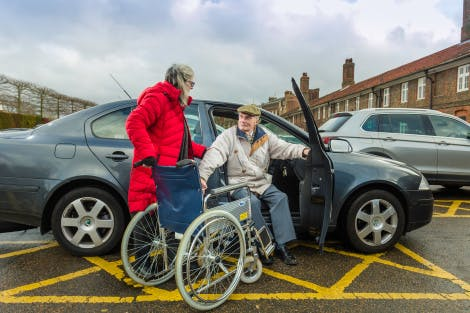 Wheelchair visitor getting out of a car parked in the disabled parking bay.
