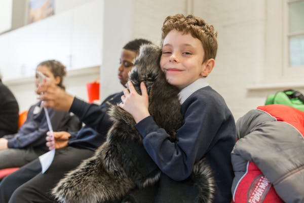 A SEND student hugs a replica fur artefact during a school session at Hampton Court Palace