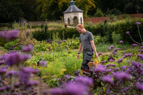 Gardener walking through the Walled Garden