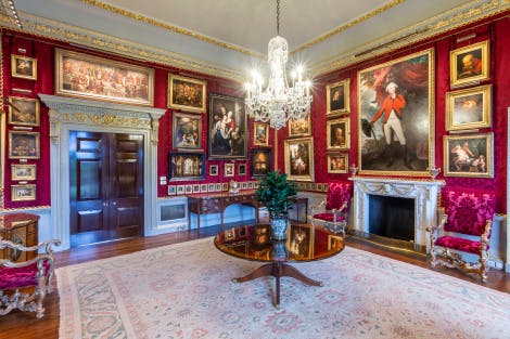 View of Red Room - walls adorned with silk red damask. Walls covered with gold-framed paintings. A Waterford Crystal chandelier hangs above a small round mahogany table.
