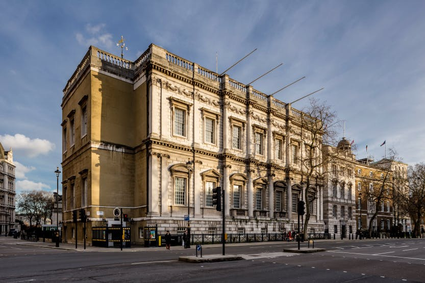 Exterior of Banqueting House under a blue hazy sky and Whitehall in the foreground
