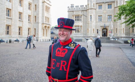 A Yeoman Warder is shown in his full uniform with the Royal Fusilier's Museum and Waterloo Block in the distance.