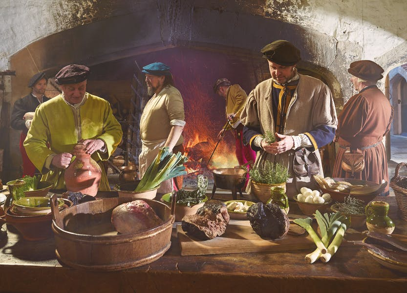 Tudor kitchen staff work in a busy backdrop of Henry VIII's kitchens at Hampton Court Palace.