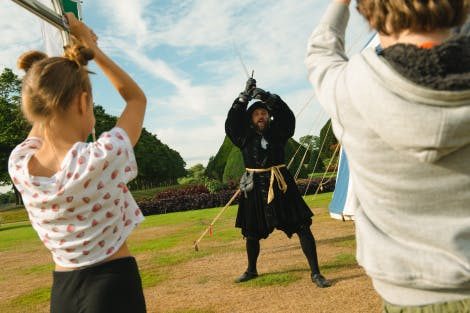Children and actors dressed in Tudor costumes enjoy a range of Tudor sports including falconry, archery, quintain and football.