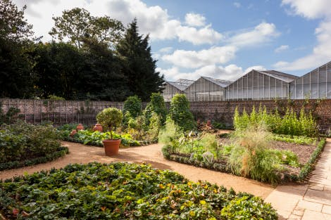 The Kitchen Garden, following conservation of the Royal Kitchens in 2013. Glasshouses are seen behind the Kitchen Garden wall in the background.