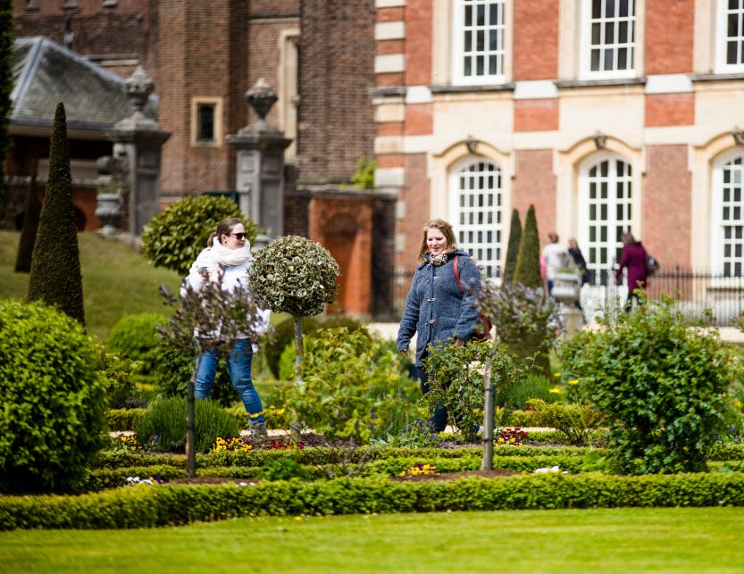 Two female visitors walking through the grounds of Hampton Court Palace.