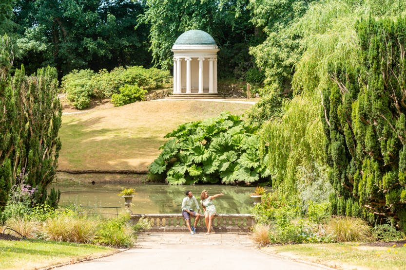 A young male and female couple sit and talk together on the stone balustrade in front of the pond, which is in front of Lady Alice's Temple. The still, calm pond is framed by mature plants and the small, white columned temple sits on a small hill above.