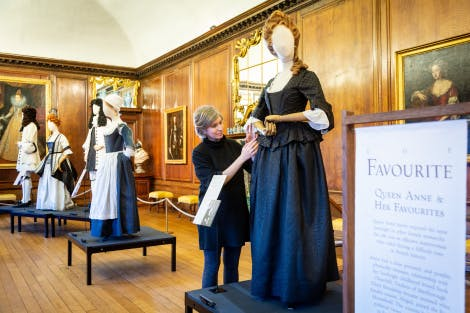 A curator attends to a black jacquered dress in a costume display in a panelled room, surrounded by paintings on the walls