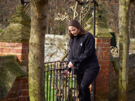 Female custody staff member stands by a metal gate and is locking or unlocking a padlock.