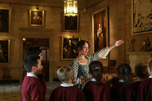 Key Stage 2 students listen to a costumed presenter at Hillsborough Castle and Gardens.