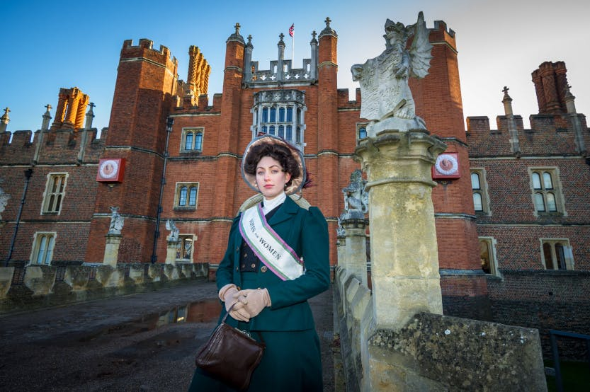 A suffragette poses outside the west front of Hampton Court Palace