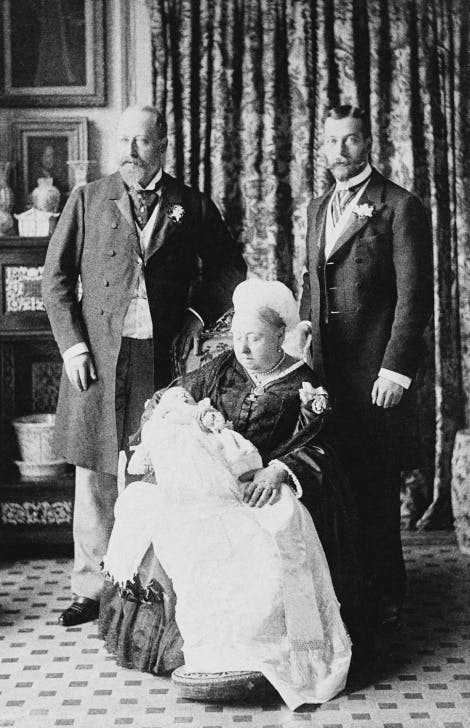 Photograph of Queen Victoria, seated, holding the infant Prince Edward of York, later the Duke of Windsor. Standing behind the Queen is Edward, Prince of Wales, later King Edward VII and Prince George of York, later King George V.