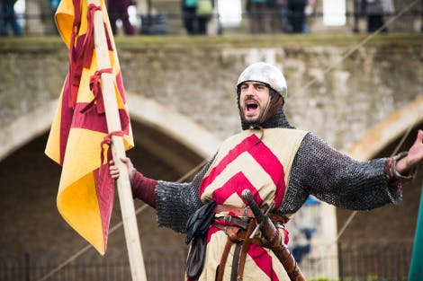 A bearded man dressed in the armour and heraldry of a 13th century knight, Gilbert de Clare, holding a banner and shouting.