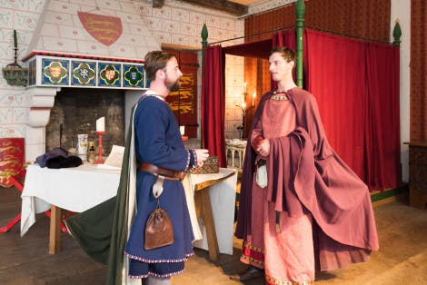 Two medieval knights, in civilian clothes, talk in the Medieval Palace