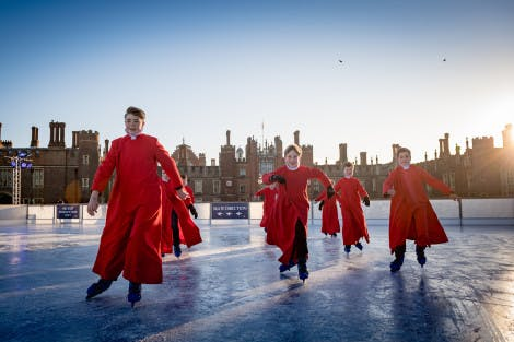 Choristers from the Chapel Royal choir skate on the ice at the Hampton Court Palace ice rinks in front of the Tudor west gate