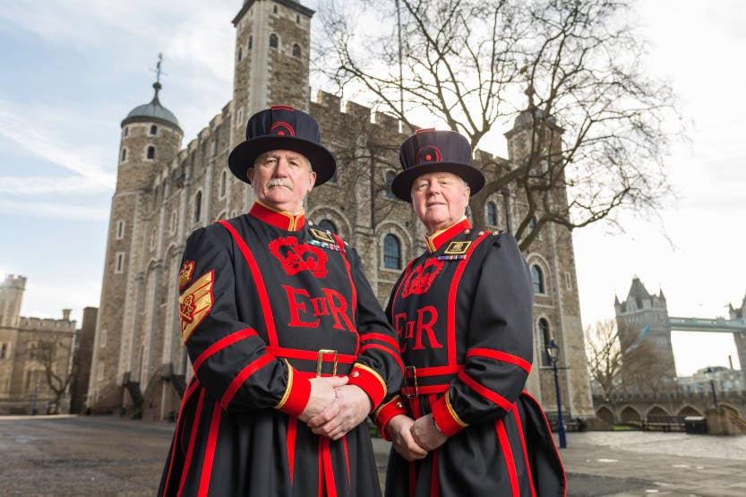 Two Yeoman Warders stand in front of the White Tower at the Tower of London dressed in uniform