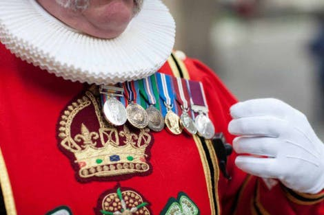 Close up detail of Yeoman Warder's ceremonial State Dress uniform. This uniform is bright red, adorned with service medals and is embossed with HRM Queen Elizabeth II's emblem in gold thread.