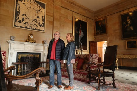 A man and woman enjoy the grandeur of the Throne Room in Hillsborough Castle.