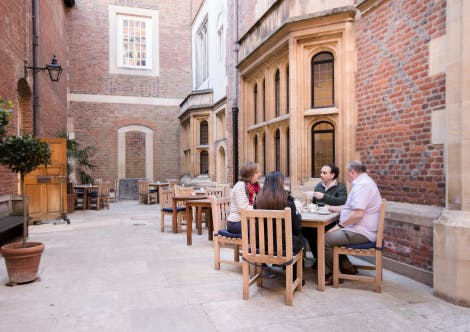 Visitors seated at a cafe table in a courtyard