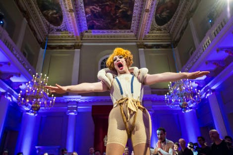 A drag artist dressed in period clothing lifts up his arms during Long Live Queen James at the Banqueting House