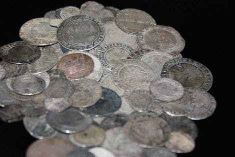 Pile of silver coins, some shiny silver, some dirty and tarnished. Coins are thin and some have damaged edges. Most are so worn you cannot see the portraits of the kings of queens on them
