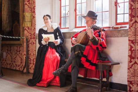 Two live interpreters dressed in Tudor costumes, recite sonnets and play instruments at Hampton Court Palace.