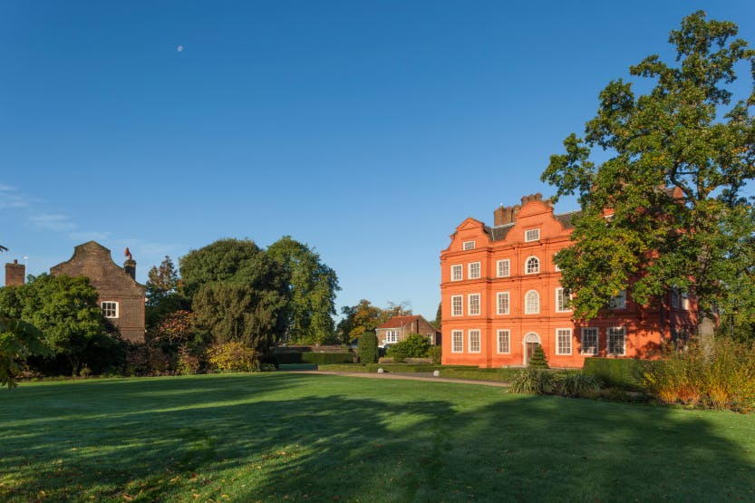 The South Front, looking from the lawn towards the Royal Kitchens. The Royal Kitchens building is partially obscured by trees and shrubs. Kew Palace stands on the right of the image. The Estates Office is seen next to Kew Palace.