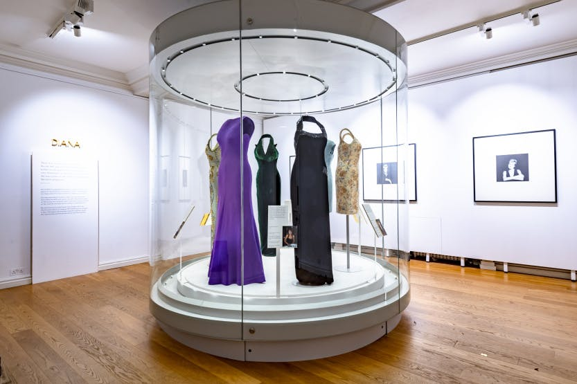 Purple and black evening dresses on display in a bright white room as part of the Diana: Her Fashion Story exhibition