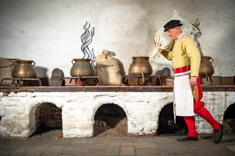 A Tudor cook carries a bag of ingredients on his shoulder past cooking pots prepared for the court in Henry VIII's Kitchens at Hampton Court Palace