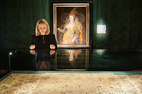 The Lost Dress of Elizabeth I exhibition, showing curator Eleri Lynn looking at the Bacton Altar Cloth in a case. The Rainbow Portrait hangs in the background of the green exhibition space.