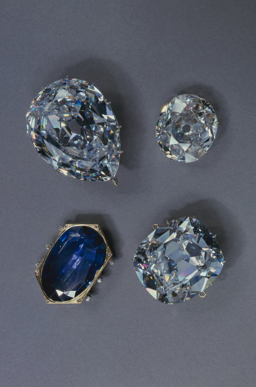 A portrait photograph of The Cullinan I and Cullinan II diamonds, the Koh-i-Noor diamond and the Stuart Sapphire from the Crown Jewels. displayed against a grey background.