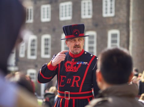 A Yeoman Warder is shown in their full uniform speaking to a group of visitors.  One arm is raised.