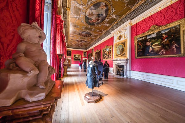 Visitors make their way down to the far end of the King's Gallery past the magnificent, gold-framed portraiture. Kensington Palace's characteristic red wallpaper can also be seen the length of the gallery