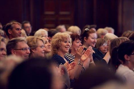 Audience members clap at an event