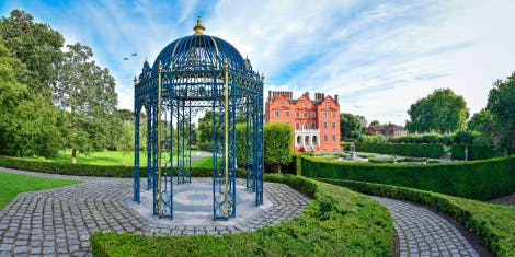 Blue metal gazebo in the Queen's Garden of Kew Palace under a cloudy blue sky looking out to the palace