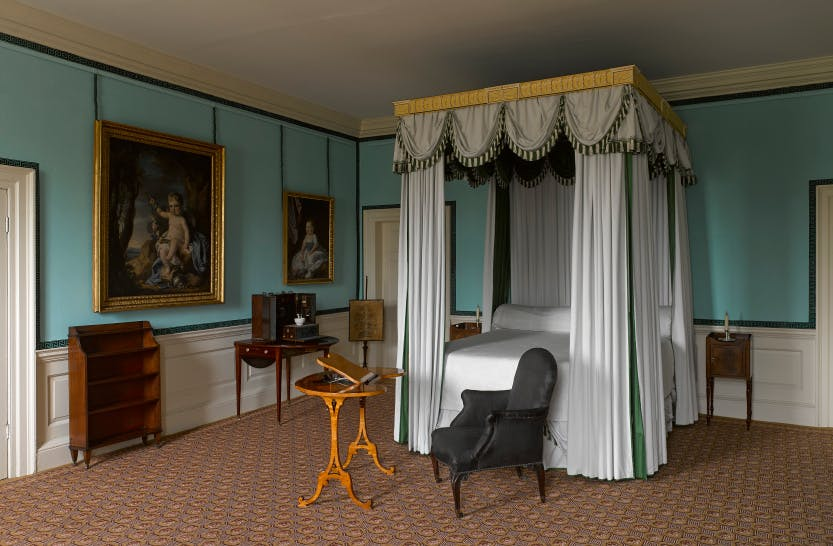 Queen Charlotte's bedroom at Kew Palace with blue walls and a four poster bed plus a black chair