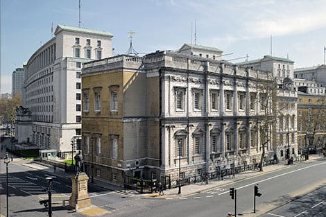 Exterior of Banqueting House with Whitehall in the foreground under a blue, partially cloudy sky