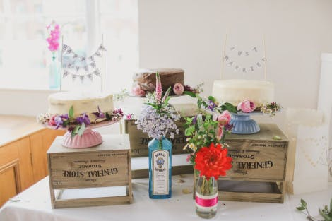 A table displays simple, rustic wedding cakes and flowers