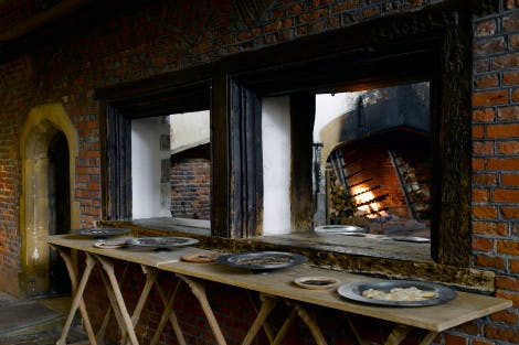 Tudor serving hatch through into a great kitchen with a roaring fire on one wall