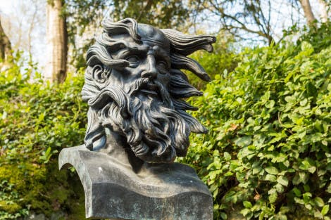 The bust of Ossian by Alexander Stoddard in the Glen at Hillsborough Castle and Gardens, in front of a green hedge