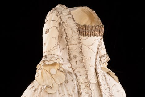 Muslin sack-back court dress, detail. Showing a view of the upper front of the dress. White Indian cotton muslin embroidered with trailing sprays of flowers and leaves in silver wire and silver strip, trimmed with silver lace and gimp. Photographed on a black background.  The sack-back was a fashionable 18th-century gown with the fabric at the back arranged in box pleats at the shoulders, falling loose to the ground with a slight train. The dress would have been worn with a wide square hoop under the petticoat.