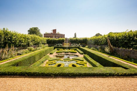 The Pond Garden at Hampton Court Palace, showing green hedging in intricate patterns. The Little Banqueting House can be seen in the background under a blue sky
