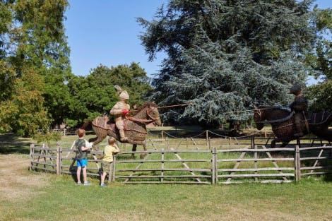 Children standing in front of the jouster wicker sculpture in Hampton Court Palace gardens.