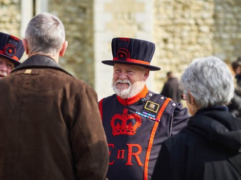 A male staff member from the Yeoman Body is shown in their full uniform/regalia speaking with a male and female visitor.