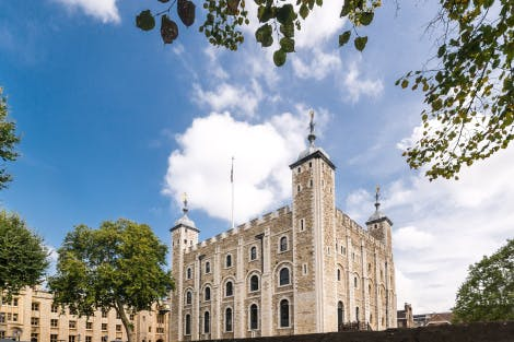 The White Tower seen against a blue, partially cloudy sky on a sunny day with foliage creeping into the upper right-hand corner. Waterloo Block can be seen in the background