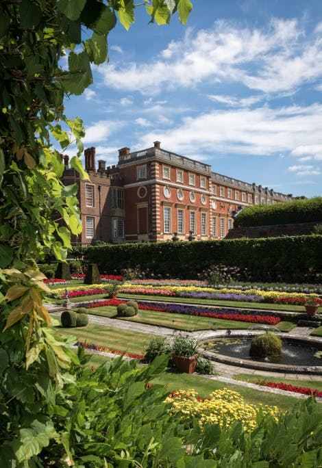 The Pond Gardens, looking north-east towards the South Front. Foliage in the foreground frames the left half of the image.