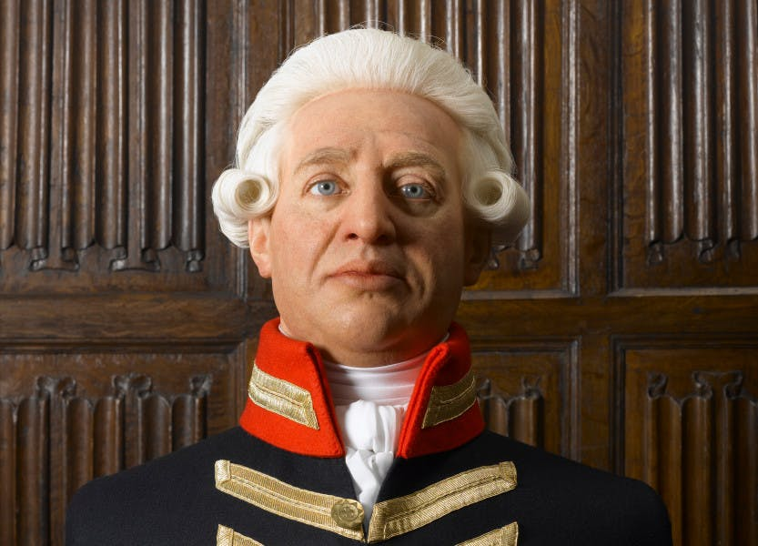 A wax bust depicting King George III in military uniform. The King wears a white period-style wig and is placed in front of a brown, linenfold panelled wall