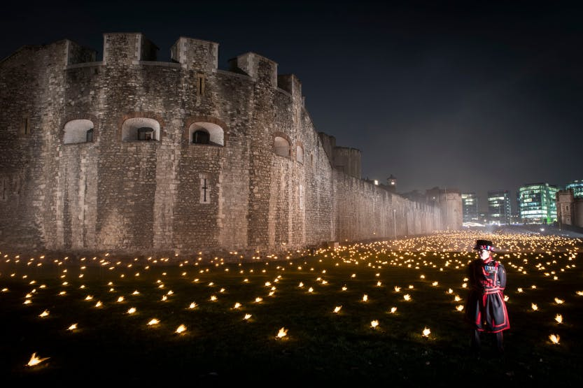 "The Tower Moat, showing Yeoman Warder Amanda Clark fulfilling her ceremonial duty at the ""Beyond the Deepening Shadow"" public event.   ""Beyond the Deepening Shadow: The Tower Remembers"" was a public act of remembrance to commemorate the centenary of the end of the First World War.  Each evening from 4 to 11 November 2018 the Tower moat was illuminated by 10,000 individual flames. The artistic installation included an exploration in sound of wartime alliances, friendship, love and loss. Beginning with a procession led by the Yeoman Warders, Armistice torches were lit to form a circle of light radiating from the Tower. A symbol of remembrance for the hundreds of thousands who died in the Great War."