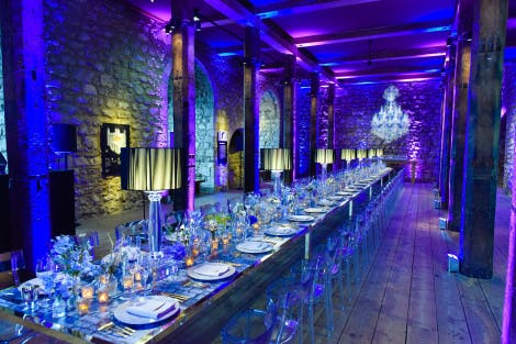 A long table set up for a dinner event at the Tower of London, with a dark blue lighted back-drop
